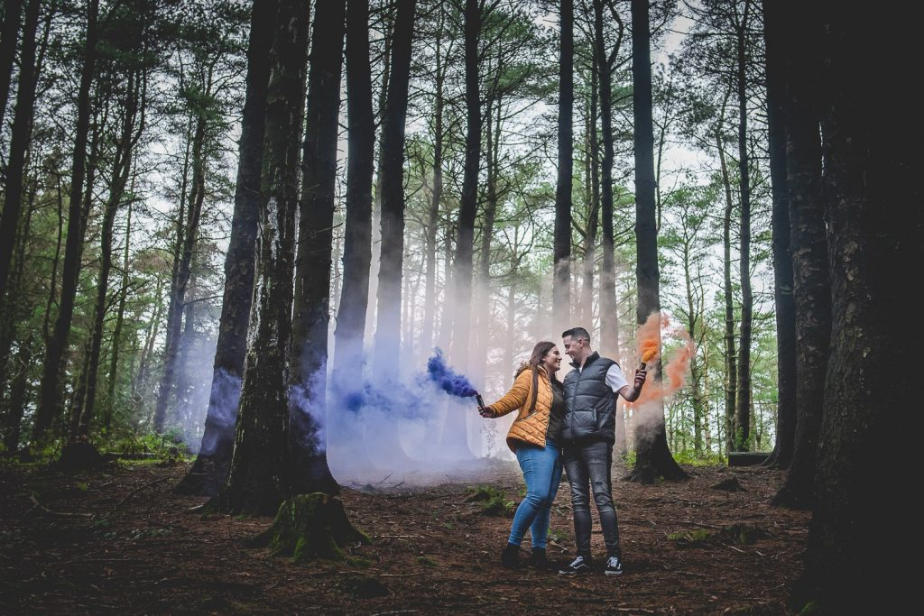 a couple standing in the woods cuddling holding an orange and purple smoke bomb